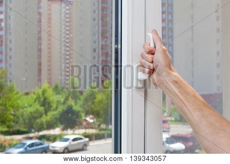 Man Hand opens a plastic pvc window