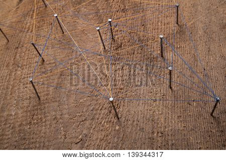 Abstract communication. Nails knotted together with thread