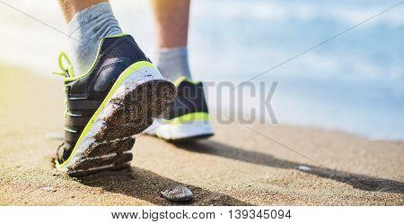 Athlete runner feet running on the coast closeup on shoe. Sport concept