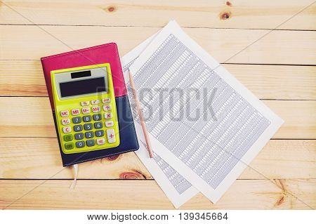 Financial accounting analysis on wooden backgroundyellow calculator pencil notebook