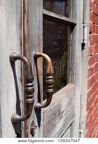 Antique door handles on wooden doors with pane glass
