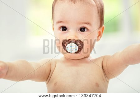 Happy cute baby with pacifier, close up