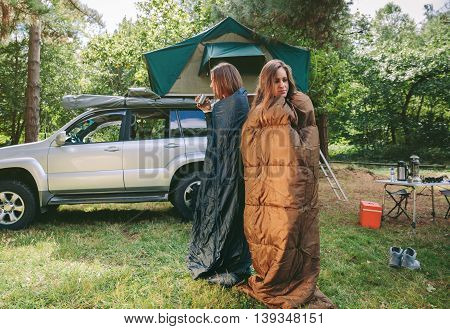Young sleepy women awakening inside of sleeping bags in a cold morning in campsite