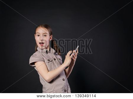 Portrait of surprised excited girl dial on touch screen of mobile phone at black background. Female child using internet in cell phone. New generation devices, communication