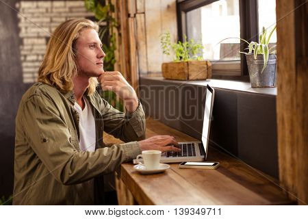 Thoughtful young man sitting at table using laptop in cafeteria