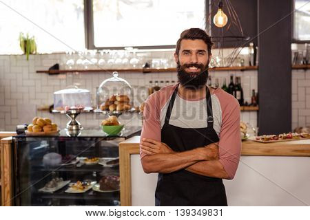 Waiter standing with arms crossed in the cafe