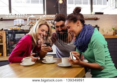Friends using smartphones sitting in the cafe