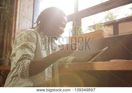 Man drinking coffee and using tablet in the cafe