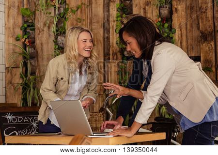 Friends using a laptop in the cafe