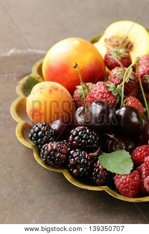 various fresh organic berries on a vintage silver plate