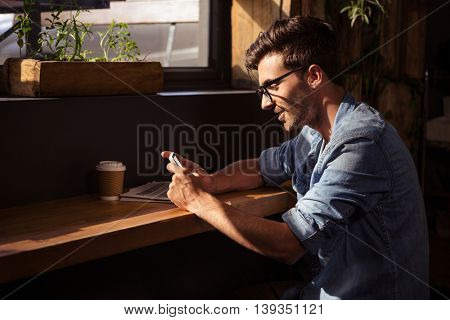Man using a smartphone in the cafe