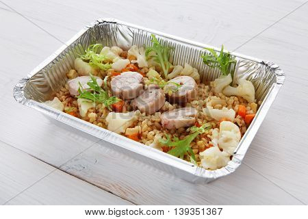 Healthy food delivery and diet concept. Take away of fitness meal. Weight loss nutrition in foil boxes. Bulgur pilaf with fish rolls and boiled cauliflowers at white wood