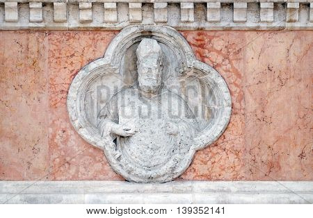 BOLOGNA, ITALY - JUNE 04: Saint Ambrose by Giovanni di Riguzzo relief on facade of the San Petronio Basilica in Bologna, Italy, on June 04, 2015