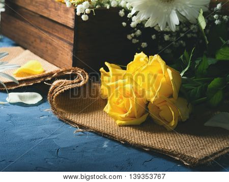 Bunch of yellow roses on blue textured background. Floral still life