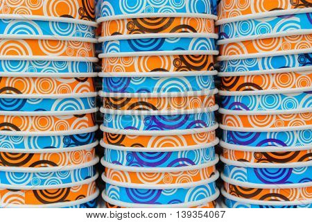 background of colored paper orange and blue cups stacked