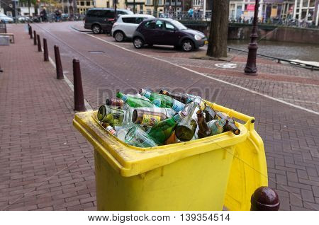 AMSTERDAM NETHERLANDS - NOVEMBER 15 2015: Yellow bin filled with empty bottles in the streets of amsterdam