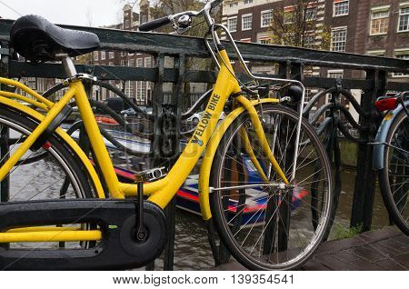 AMSTERDAM - NOVEMBER 15 2015: Yellow rental bike on a bridge. The number of bicycles equal the number of residents in the dutch capital