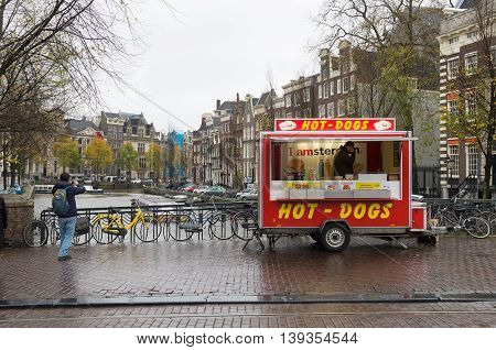 AMSTERDAM NETHERLANDS - NOVEMBER 15 2015: Vendor with a hot-dogs stall on a rainy day in the center of amsterdam