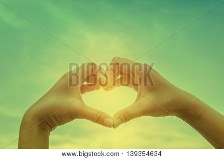 Beautiful woman hand making a heart shape on blue sky background