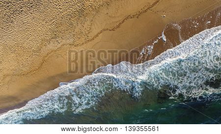 Aerial image of sea waves crashing on a lonely beach in a late summer afternoon.