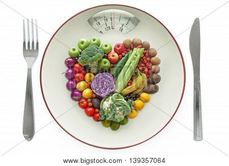 Diet concept, plate with weighing scales packed with fruits and vegtables in a heart shape