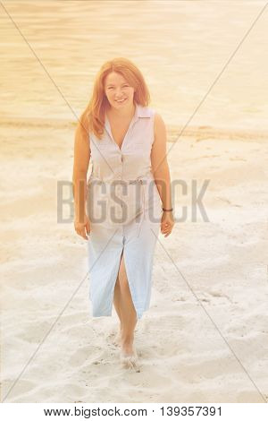 Toned picture of beautiful mature red-haired woman in blue summer dress walking near by sea. Happy lady smiling and looking at camera.