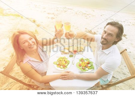 Closeup toned top image of happy mature couple looking at camera and holding glasses of white wine while having date in restaurant or cafe by sea.