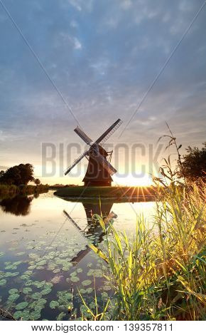 gold sunshine behind Dutch windmill by river Holland