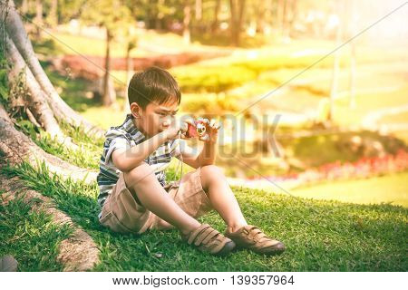 Asian Boy With Camera Relaxing Outdoors In The Day Time, Travel On Vacation.