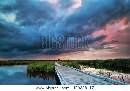 wooden bike road on water and storm during sunset