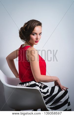 beautiful young woman sitting in the chair gracefully.