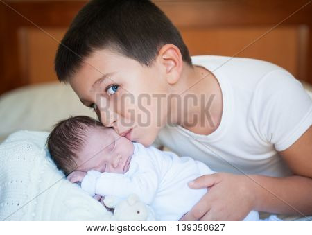 Happy boy next to her newborn brother