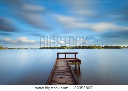 wooden pier on big lake and blurred sky due long exposure