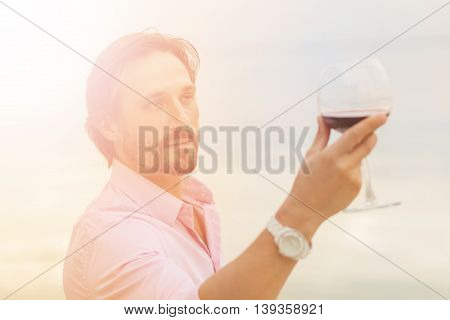 Toned picture of sommelier analyzing glass of red wine isolated on blue sky background. Black-haired mature man happy looking at glass.