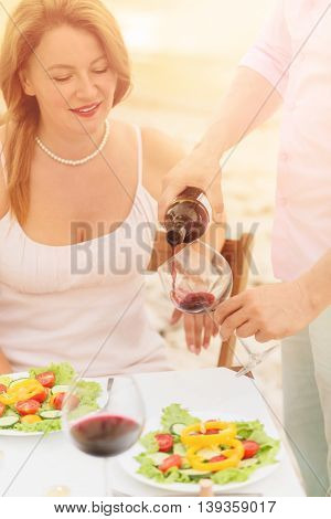 Toned picture of professional sommelier demonstrating red wine to beautiful woman. Red-haired woman looking at sommelier pouring red wine in her glass.