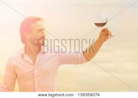 Toned picture of satisfied mature professional sommelier looking at glass with red wine. Handsome man in pink shirt drawing aside glass.