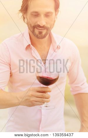Confident and happy sommelier. Toned image of bearded mature man in pink shirt tasting red wine and looking at glass isolated on sea.