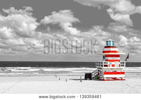 modern life guard house or beach patrol tower white and red color on ocean or sea water coast with sand and cloudy sky copy space black and white