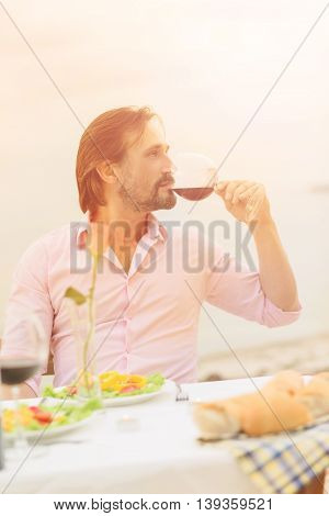 Toned portrait of handsome man drinking red wine while resting in restaurant or cafe by sea. Bearded man in pink shirt spending time abroad or outskirts.