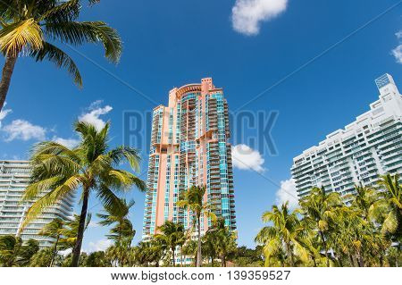 Architectural luxury flat building Miami Style South Beach Florida Modern art deco condominium construction aqua and apricot color with palm trees against blue tropical sky background