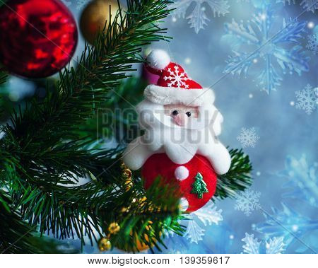 Christmas toy Santa Claus hanging on artificial Christmas tree