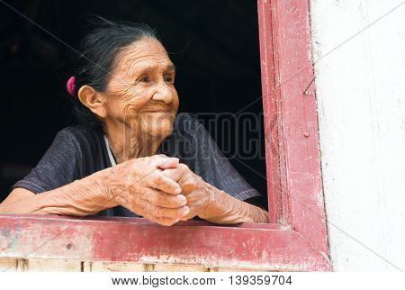 Boca de Valeria Brazil - December 03 2015: old mature mulatto woman with kind smiling face holding hands together standing in wooden window brown and white color looking outdoor