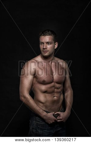 Young sexy handsome athletic man with naked torso on dark background with copyspace