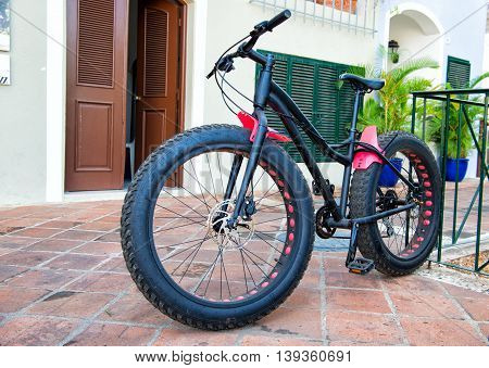 cool sport bicycle with iron and plastic hull and big rubber tyre wheels black color standing on stony road outdoor with nobody