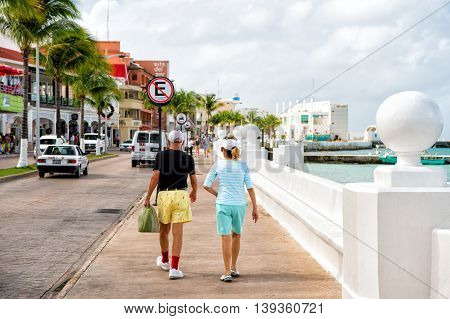 Cozumel, Mexico - December 24, 2015: SENIOR couple of well dressed woman and man walking on street promenade near bay with water and palm trees and cars outdoor in summer