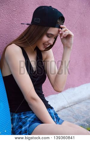 Portrait of pretty stylish young girl wearing cap and jeans shorts over pink wall