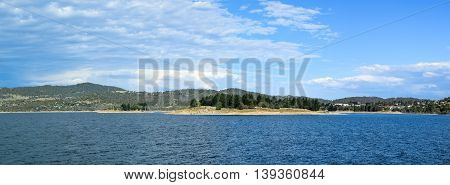 Lake Jindabyne landscape with a blue sky and some clouds.  The lakes two largest islands are pictured in the centre -  'Lion Island' (right) and 'Cub Island' (left).  Jindabyne township can be seen to the right of Lion Island.