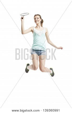 beautiful young girl playing with badminton racket in sneakers over white background