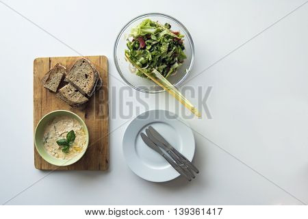 Cheese spread & baked bread with fresh summer salad. Flat lay food on white wooden table.
