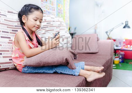 Portrait of cute asian Thai little girl playing mobile phone at home with copy space shallow depth of field